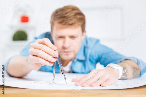 Foto Murales Scrupulous worker. Serious busy clever engineer feeling concentrated while frowning and measuring the length with a help of a pair of compasses