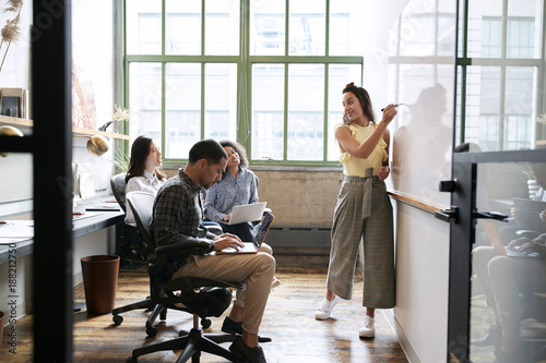 Height scale Woman using whiteboard in a small team meeting