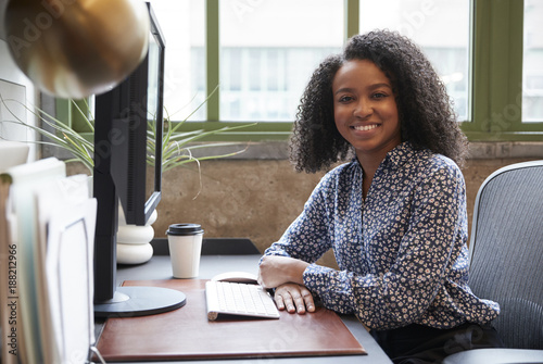 Poster Black woman at a computer in an office smiling to camera