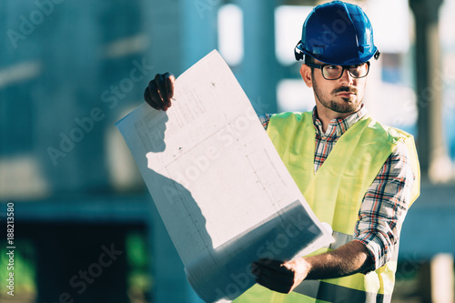 Picture of construction site engineer looking at plan