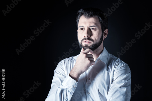 Foto Murales Being thoughtful. Pleasant nice handsome man looking in front of him and thinking while standing against black background