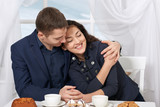 happy couple drinking coffee and talking near window with a sky view - travel and love concept