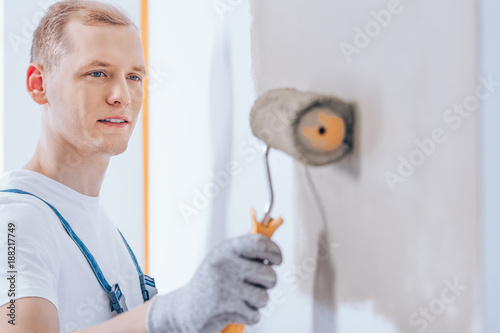Worker using a paint roller