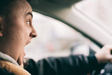 Screaming man driving a car.