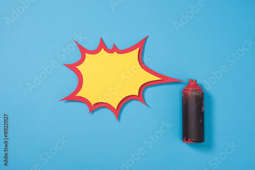 top view of spray paint in can and empty paper speech bubble isolated on blue - 188220127