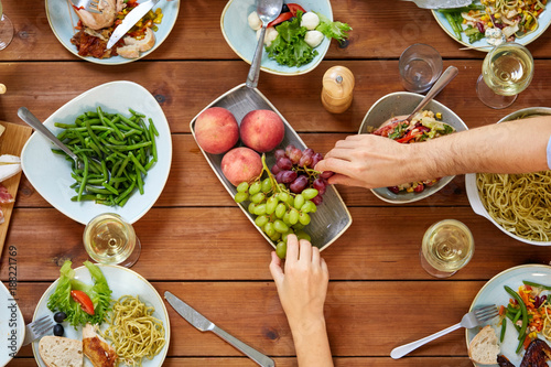 Foto Murales group of people eating at table with food