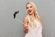 Portrait of a joyful girl holding paper moustache on stick