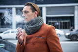Side view serious male inhaling tobacco while walking outdoor. Rest concept - 188233728