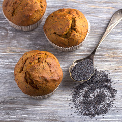 Three delicious homemade pumpkin muffins with cinnamon and poppy seeds on wooden surface, top view, selective focus