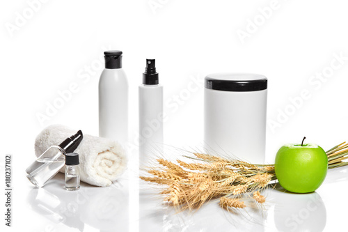 Foto op Canvas Spa Spa cosmetics, jar of cream, oil with wheat, white cosmetic bottles with apple and wheat towel, candle, soap isolated on white. Without label.