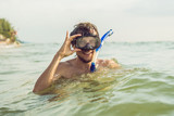 A man with a mask and snorkel is going to dive into the sea - 188249507