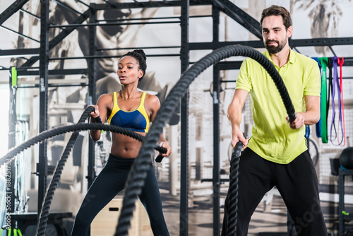 Fridge magnet People doing functional training with battle rope in crossfit gym