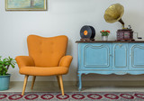 Vintage interior of retro orange armchair, vintage wooden light blue sideboard, old phonograph (gramophone), vinyl records on background of beige wall, tiled porcelain floor, and red carpet - 188254565