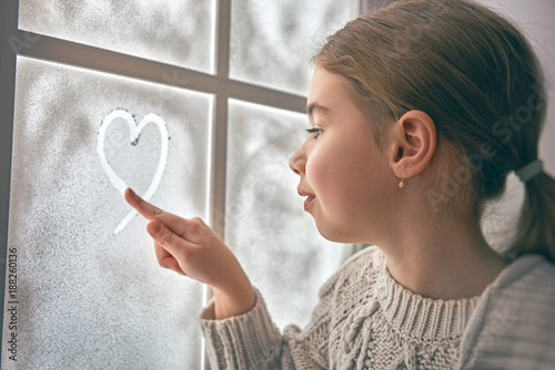 Foto Murales girl sitting by the window
