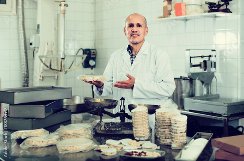 Foto Murales Portrait of  mature male with packing of turron in food factory