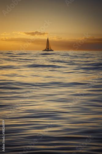 Fotobehang Zeilen Sailboat floating at sea during golden sunset