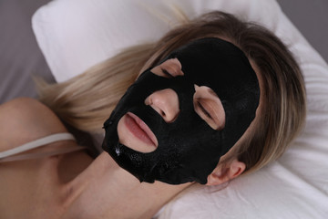 Young beautiful woman applying black facial mask . Skin care, beauty treatments.