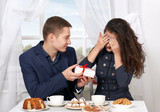 happy couple drinking coffee and having fun, give gifts near window with a sky view - love and holiday concept
