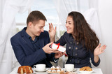 happy couple drinking coffee and having fun, man give very funny gifts - love and holiday concept