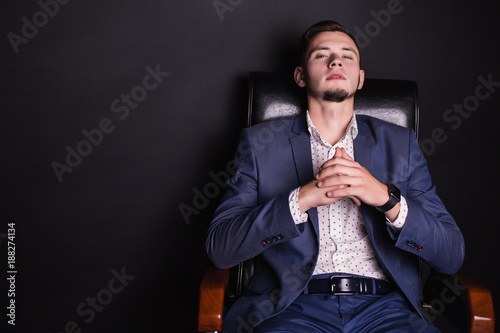 A successful young businessman in a business suit and white shirt and a fashionable watch on his arm on a black leather chair. Stylish man. Director of the firm