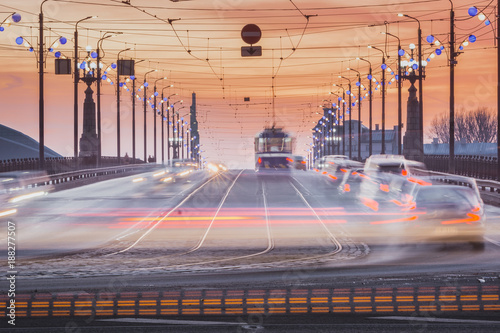 Fridge magnet Sunset in Riga city with cars crossing the bridge creating light trails. Picturesque view on the highway with colorful sky.
