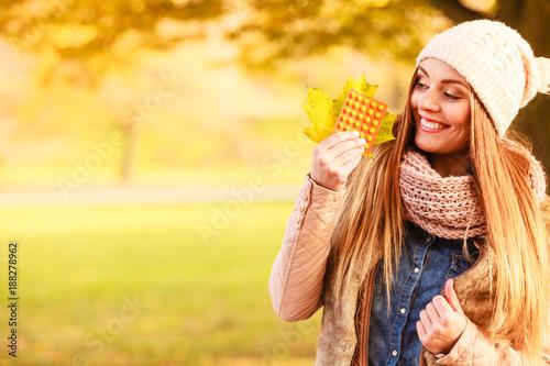 Foto Murales Woman in autumn park holding vitamins medicines