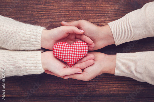 Female and male hand holding red fabric heart on brown background