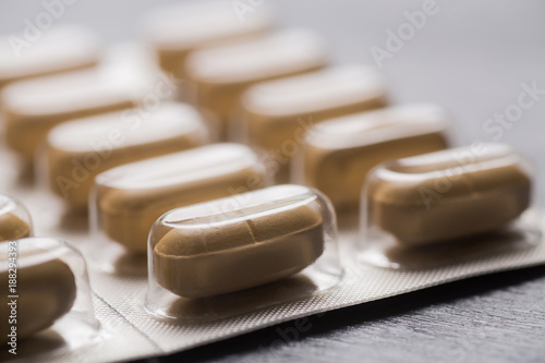 Closeup yellow long tablets in blister pack on gray background