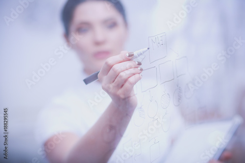 Young woman drawing on whiteboard with white copyspace. Young woman