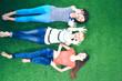 Young women lying on green grass . Young women