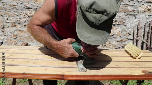 The worker diligently cleans and polishes the iron parts of the old door in the rustic environment with a modern polishing tool.