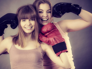 Two women friends wearing boxing gloves