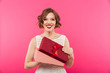 Portrait of a happy girl dressed in dress holding gift box
