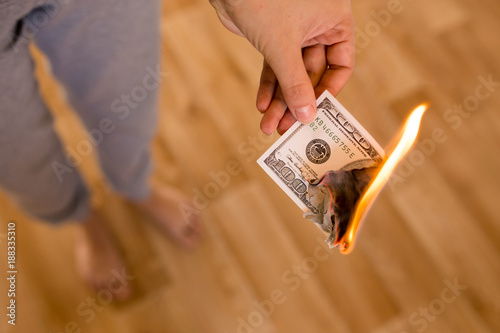 one hundred dollars burn in flames in hand