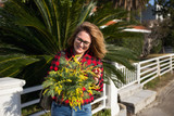Happy woman with a bouquet of yellow mimosa flowers. Sunny day, the sea coast. The girl laughs, standing near the palm tree. - 188341395
