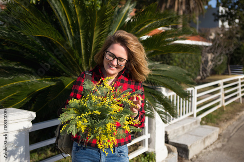 Foto Murales Happy woman with a bouquet of yellow mimosa flowers. Sunny day, the sea coast. The girl laughs, standing near the palm tree.