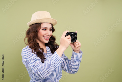 Foto Murales Young asian female traveler in casual clothing holding an amateur digital camera.