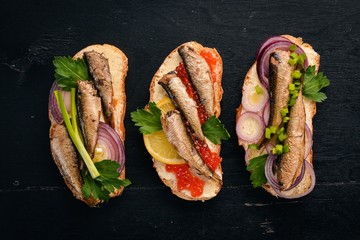 A set of sandwiches with sprats, and caviar, onion and parsley, on a wooden background. Top view. Copy space.