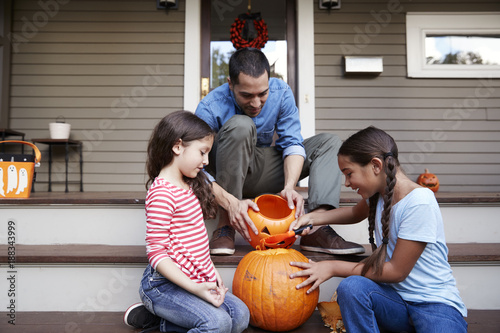 Foto Murales Father And Daughters Carving Halloween Pumpkin On House Steps