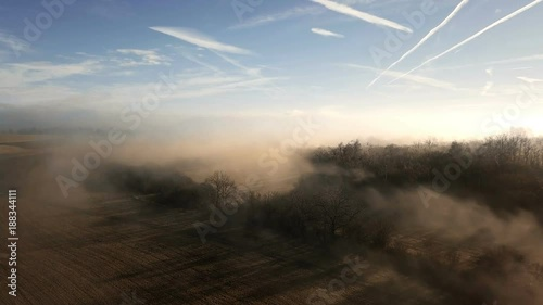 Aerial misty morning landscape with sun beam over tree in countryside