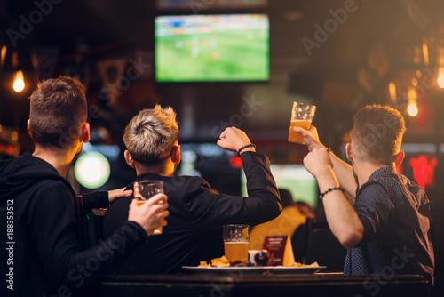 Three men watches football on TV in a sport bar - 188353512