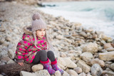 Portrait of cute little girl playing on the beach
