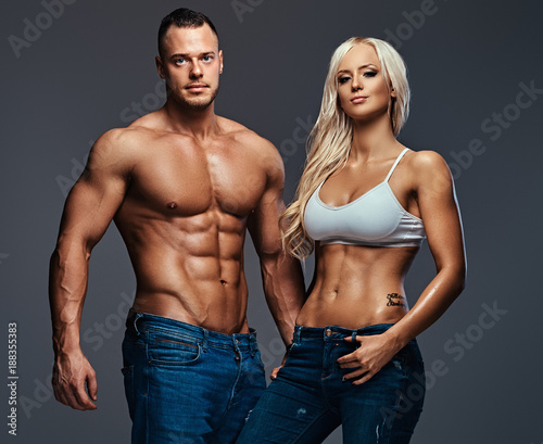 Poster Attractive fitness couple over grey background.