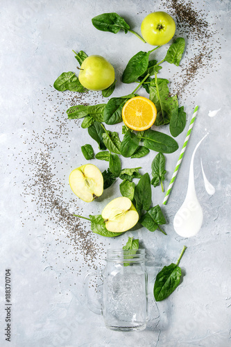 Foto Murales Detox drink concept. Ingredients for smoothie green spinach leaves, apple, orange, yogurt splash, mason jar, cocktail tube over gray texture background. Healthy vegan eating. Top view, space