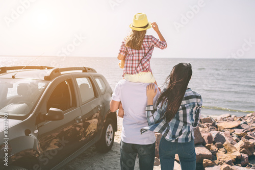 Happy family standing near a car on the beach. Happy family on a road trip in their car. Dad, mom and daughter are traveling by the sea or the ocean or the river. Summer ride by automobile