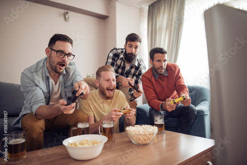 Happy young male friends playing video games at home