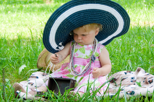 The baby girl in big hat sitting on the grass with jewelery.