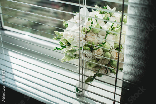Foto Murales wedding bouquet of white roses on a window sill with jalousie