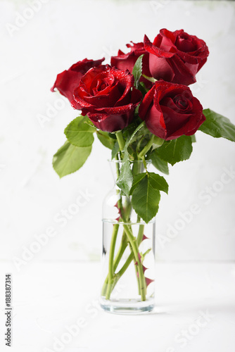 Foto Murales Red fresh roses on the white table