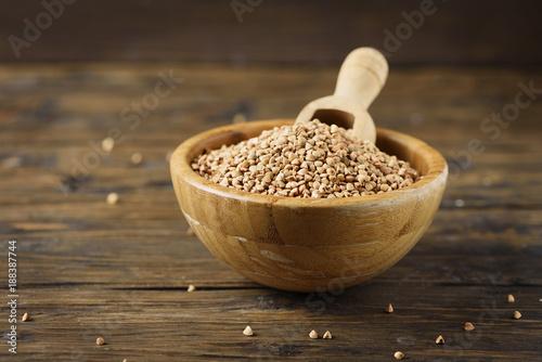 Foto Murales Raw buckwheat grain on the wooden table